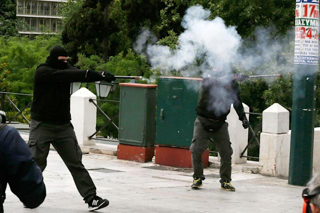 <p>Protesters aim with a flare gun to the riot police during clashes at a nationwide general strike demonstration, in Athens, Wednesday, May 17, 2017. Greek workers walked off the job across the country Wednesday for an anti-austerity general strike that was disrupting public and private sector services across the country. (AP Photo/Thanassis Stavrakis) </p>