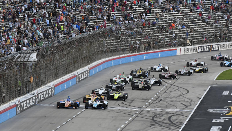 FILE - In this June 8, 2019, file photo, drivers jockey for position at the start of an IndyCar auto race at Texas Motor Speedway in Fort Worth, Texas. IndyCar is getting ready for an all-in-one-day season opener on the fast track in Texas, more than 2 ½ months after drivers were set to roll on the streets of St. Pete. The pandemic-delayed season is now set to open Saturday, June 6, 2020. (AP Photo/Larry Papke, File)