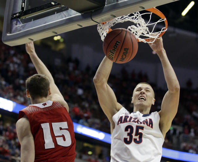 Arizona's Kaleb Tarczewski dunks past Wisconsin 's Sam Dekker (15) during the first half in a regional final NCAA college basketball tournament game, Saturday, March 29, 2014, in Anaheim, Calif. (AP Photo/Alex Gallardo)