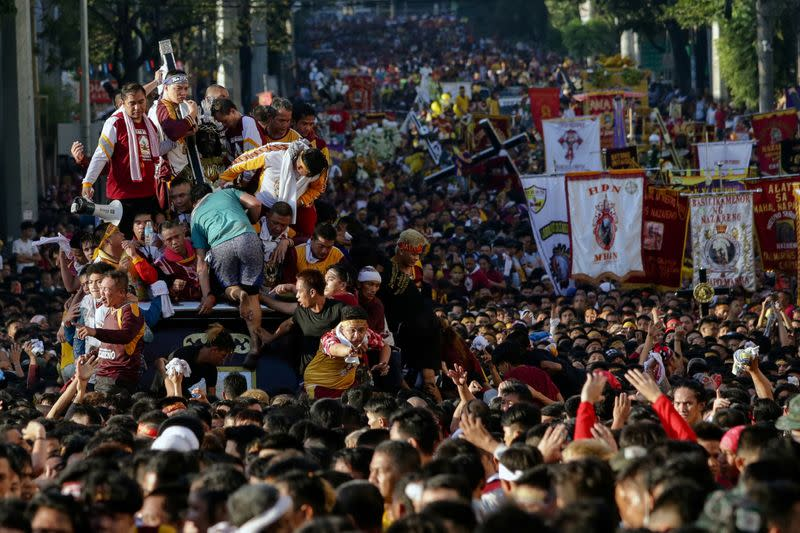 Filipino devotees attempt to climb and touch the Black Nazarene during the annual procession celebrating its feast day in Manila