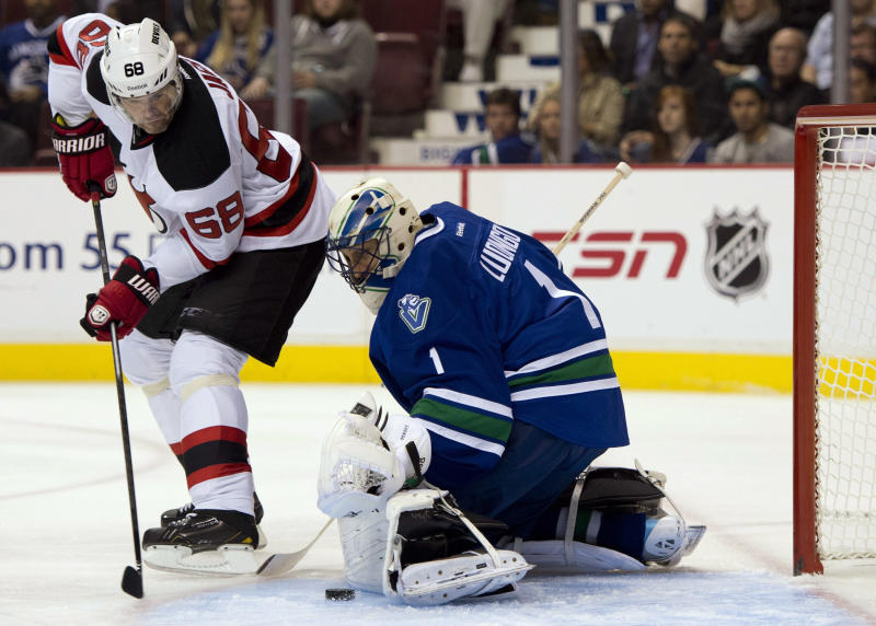 New Jersey Devils right wing Jaromir Jagr (68) tries to get a shot past Vancouver Canucks goalie Roberto Luongo (1) during the first period of an NHL hockey game Tuesday, Oct. 8, 2013, in Vancouver, British Columbia. (AP Photo/The Canadian Press, Jonathan Hayward)