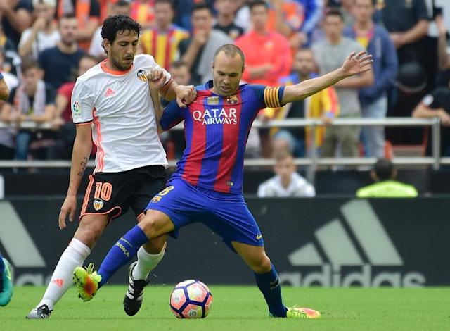 Valencia's midfielder Dani Parejo (L) vies with Barcelona's midfielder Andres Iniesta during the Spanish league football match between Valencia CF and FC Barcelona at the Mestalla stadium in Valencia on October 22, 2016 (AFP Photo/Jose Jordan)