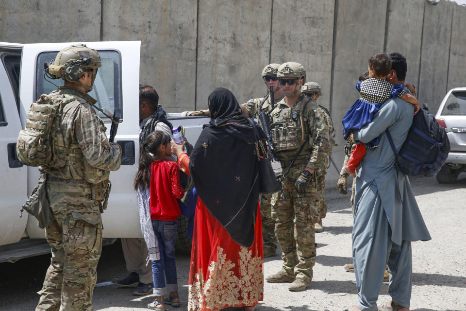 In this image provided by the U.S. Marines, soldiers assigned to 3rd Brigade, 10th Mountain Division escort evacuees to the terminal for check-in during an evacuation at Hamid Karzai International Airport in Kabul, Afghanistan, Friday, Aug. 20, 2021. (Lance Cpl. Nicholas Guevara/U.S. Marine Corps via AP)