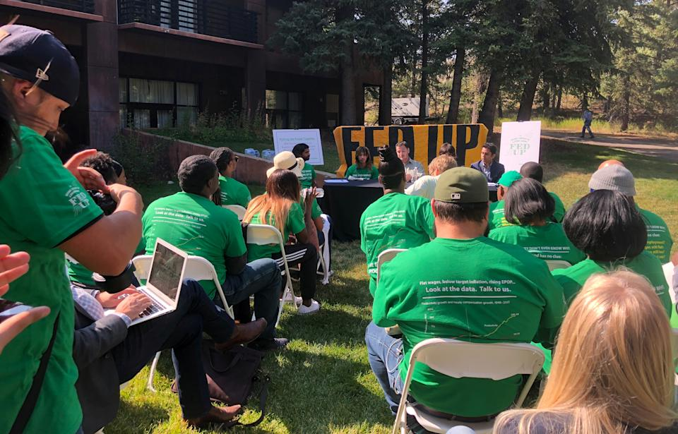Members of labor activist group Fed Up holds a meeting outside of Jackson Lake Lodge in Jackson Hole, Wyoming, U.S., August 23, 2018, on the eve of the Kansas City Federal Reserve Bank's annual economic symposium. REUTERS/Ann Saphir