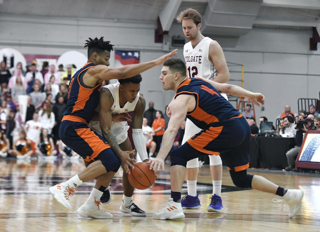 Colgate guard Jordan Burns, center, tries to split the defense of Bucknell guard Avi Toomer, left, and center Nate Sestina during the second half of an NCAA college basketball game for the championship of the Patriot League men's tournament in Hamilton, N.Y., Wednesday, March 13, 2019. Colgate won 94-80. (AP Photo/Adrian Kraus)