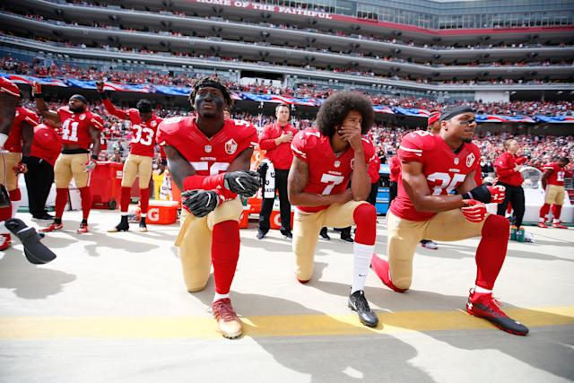 Antoine Bethea and Rashard Robinson raise their fists during the national anthem as Eli Harold, left, Colin Kaepernick and Eric Reid take a knee prior to a game against the Dallas Cowboyson Oct. 2, 2016.
