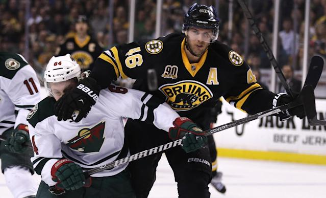 Boston Bruins center David Krejci (46) holds back Minnesota Wild center Mikael Granlund (64) as they chase the puck during the second period of an NHL hockey game, Monday, March 17, 2014, in Boston. (AP Photo/Charles Krupa)
