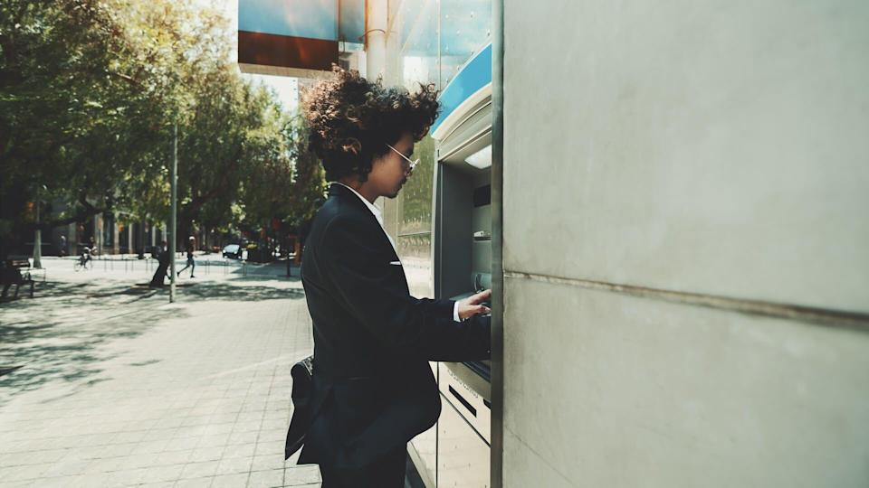 Side view of curly man in foraml suit using street ATM to withdraw cash from his account; a businessman is using an outdoor cash dispenser to increase his account.