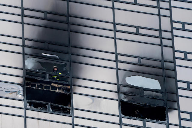 <p>A firefighter looks out from the window of a damaged apartment in Trump Tower in New York on Saturday, April 7, 2018. (Photo: Craig Ruttle/AP) </p>