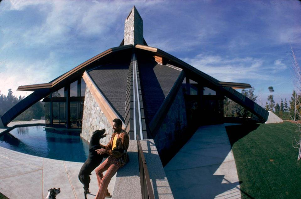 <p>Wilt Chamberlain plays with one of his pet dogs outside his specially-commissioned home, called Ursa Major, in Bel-Air, California in 1972.</p>