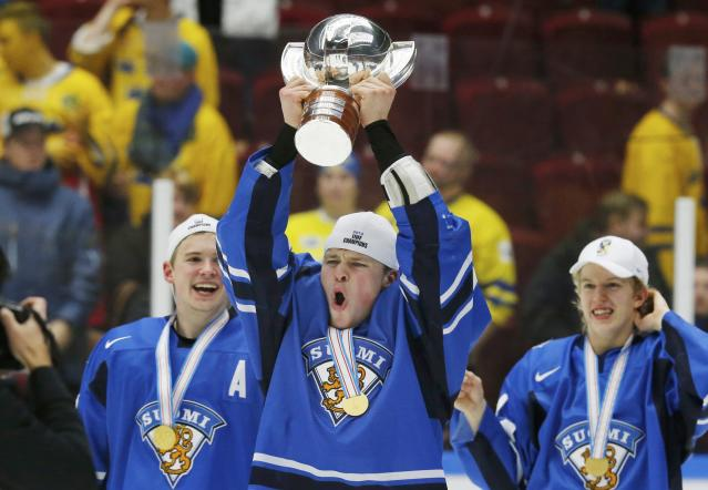 Finland's Mikko Lehtonen celebrates with the trophy after his team defeated Sweden in overtime of their IIHF World Junior Championship gold medal ice hockey game in Malmo, Sweden, January 5, 2014. REUTERS/Alexander Demianchuk (SWEDEN - Tags: SPORT ICE HOCKEY)
