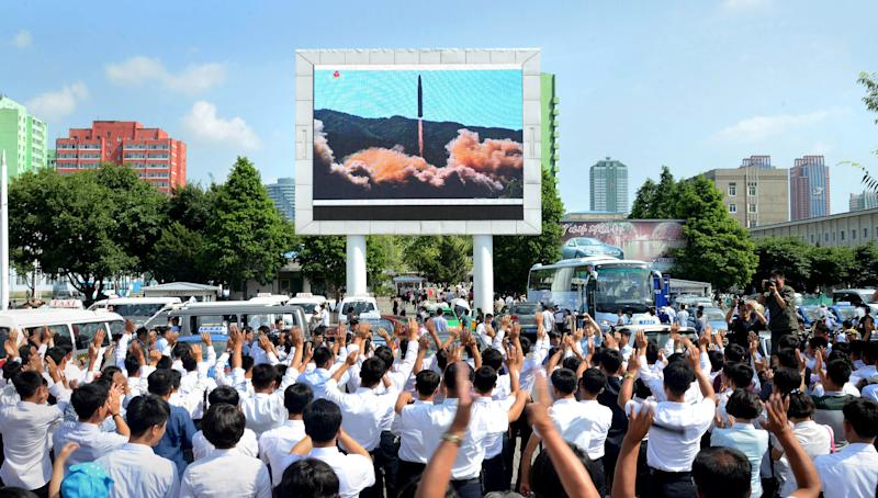 North Koreans celebrate the test launch of an intercontinental ballistic missile earlier this year