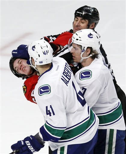 Chicago Blackhawks center Andrew Shaw, left, is bent back by Vancouver Canucks defenseman Andrew Alberts (41) and David Booth as a referee tries to break them up during the second period of an NHL hockey game in Chicago, Wednesday, March 21, 2012. (AP Photo/Charles Rex Arbogast)