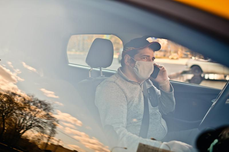 Taxi driver wearing protective medical mask parked on a city street and uses smartphone during an illness epidemic