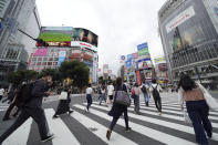 People wearing protective masks to help curb the spread of the coronavirus walk along a pedestrian crossing Thursday, June 24, 2021, in Tokyo. (AP Photo/Eugene Hoshiko)