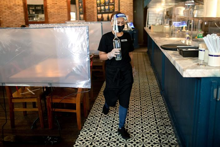 """A waitress wears personal protective equipment while working at a restaurant where plastic barriers are installed in-between tables in Metro Manila, Philippines, June 16, 2020. <p class=""""copyright"""">REUTERS/Eloisa Lopez</p>"""