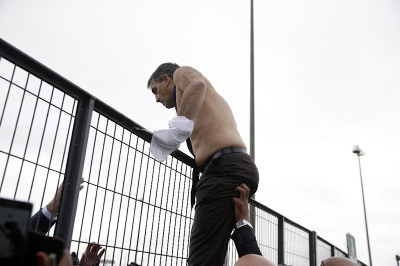 Air France's human resources manager Xavier Broseta was forced to jump over a fence, to escape angry workers who stormed the airline's offices in Roissy-en-France, on October 5, 2015 (AFP Photo/Kenzo Tribouillard)