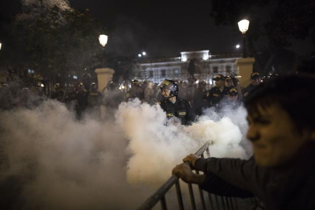 Police launch tear gas at supporters of President Martin Vizcarra to keep them from forcibly entering Congress after the president dissolved the legislature in Lima, Peru, Monday, Sept. 30, 2019. Vizcarra dissolved congress Monday, exercising seldom used executive powers to shut down the opposition-controlled legislature that he accuses of stonewalling attempts to curb widespread corruption. (AP Photo/Rodrigo Abd)