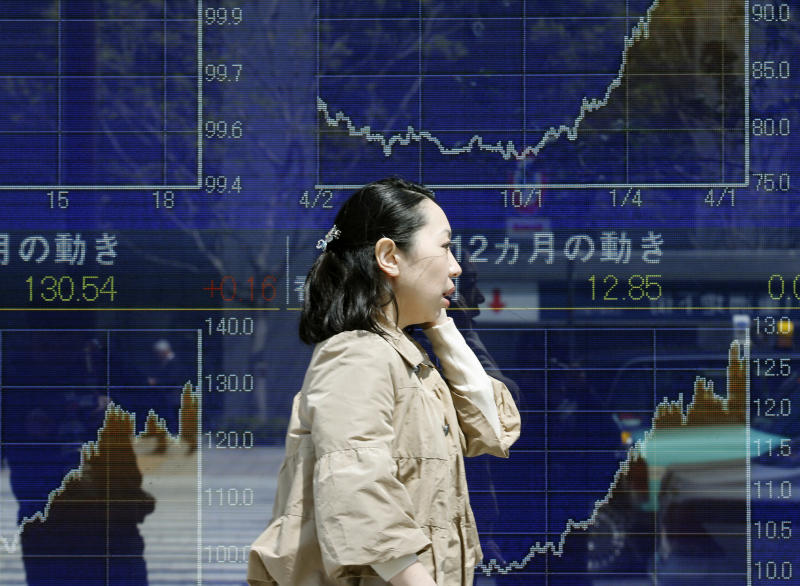 A woman walks by an electronic stock board of a securities firm in Tokyo, Monday, April 22, 2013. Asian markets traded higher Monday, with Tokyo stock markets heading close to a five-year high after a meeting of global finance leaders lent support to Japan's aggressive monetary policy. (AP Photo/Koji Sasahara)
