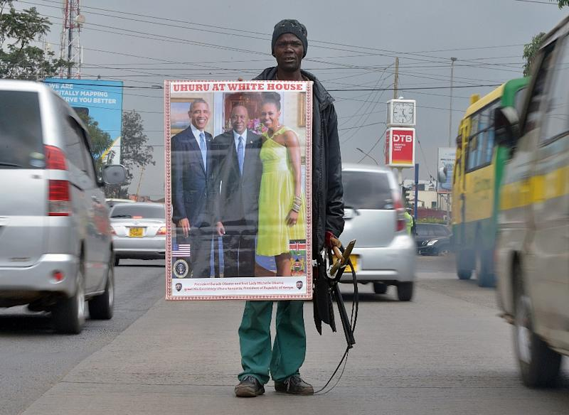 A street vendor shows a photo of US President Barack Obama (L) and first lady Michelle Obama (R) with Kenya's President Uhuru Kenyatta to passing motorists in Nairobi on July 9, 2015 (AFP Photo/Tony Karumba)