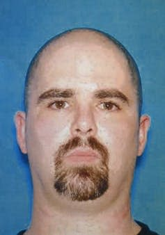 Head shot of a balding white man with a goatee against a blue background