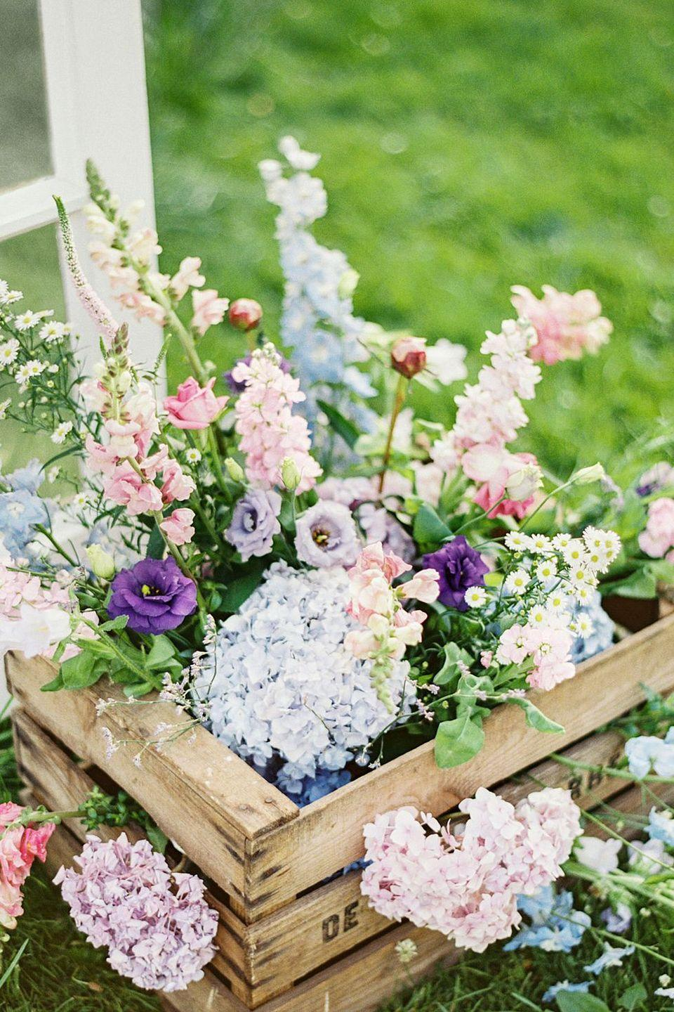 """<p>Hydrangeas, lisianthus and, snapdragons will be in their element when placed in a rustic crate, which can also be left out on your front porch. </p><p><em><a href=""""https://www.countryliving.com/entertaining/g733/spring-table-settings-0209/?slide=12"""" rel=""""nofollow noopener"""" target=""""_blank"""" data-ylk=""""slk:Get the tutorial from Country Living »"""" class=""""link rapid-noclick-resp"""">Get the tutorial from Country Living »</a></em></p>"""