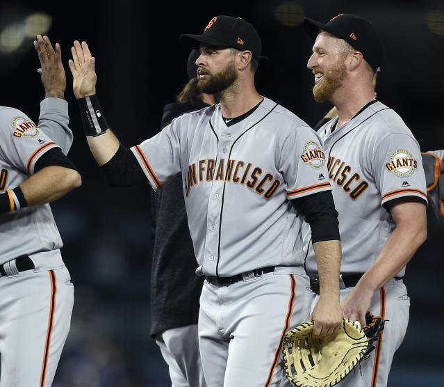 San Francisco Giants' Brandon Belt, center, celebrates with his team in front of relief pitcher Will Smith after a baseball game in Los Angeles, Monday, April 1, 2019. The Giants won 4-2. (AP Photo/Kelvin Kuo)