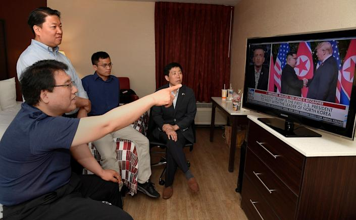 North Korean defectors Park Sang Hak and Justin Kim watch replays of President Donald Trump's summit meeting in Singapore.