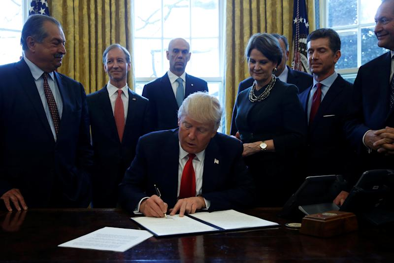 U.S. President Donald Trump is surrounded by business leaders as he signs an executive order on regulatory reform at his desk in the Oval Office at the White House, U.S. February 24, 2017. REUTERS/Jonathan Ernst