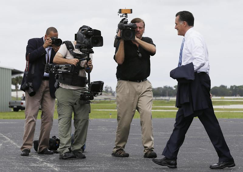Republican presidential candidate and former Massachusetts Gov. Mitt Romney is filmed by a television news camera crew and his campaign photographer as he steps off his charter plane in Sarasota, Fla., Thursday, Sept. 20, 2012. (AP Photo/Charles Dharapak)