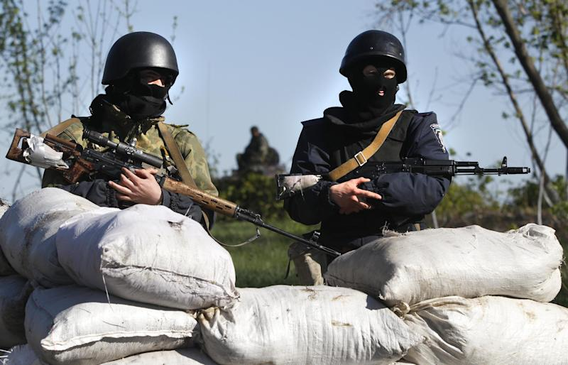 Ukrainian government troops guard a checkpoint near the village of Dolina, 30 kilometers (18 miles) from Slovyansk, eastern Ukraine, Saturday, April 26, 2014. Ukrainian authorities are undertaking a security operation to liberate the nearby city of Slovyansk, which is currently controlled by an armed pro-Russian insurgency. (AP Photo/Sergei Grits)