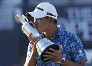 United States' Collin Morikawa kisses the claret jug trophy as he poses for photographers on the 18th green after winning the British Open Golf Championship at Royal St George's golf course Sandwich, England, Sunday, July 18, 2021. (AP Photo/Peter Morrison)
