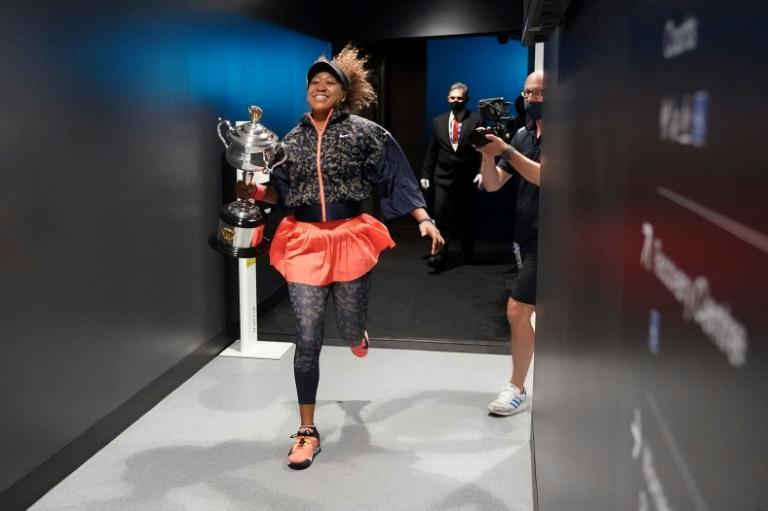 A celebrating Naomi Osaka runs with the trophy behind the scenes at Rod Laver Arena after her Australian open final win