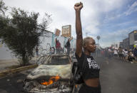 A protester poses for photos next to a burning police vehicle in Los Angeles on May 30, 2020, during a demonstration over the death of George Floyd. (AP Photo/Ringo H.W. Chiu)