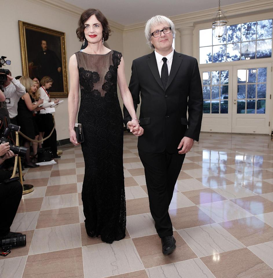 Actress Elizabeth Lee McGovern, left, and Simon Adam Curtis arrive at the Booksellers area of the White House in Washington for the State Dinner hosted by President Barack Obama and first lady Michelle Obama for British Prime Minister David Cameron and his wife Samantha, Wednesday, March 14, 2012. (AP Photo/Charles Dharapak)
