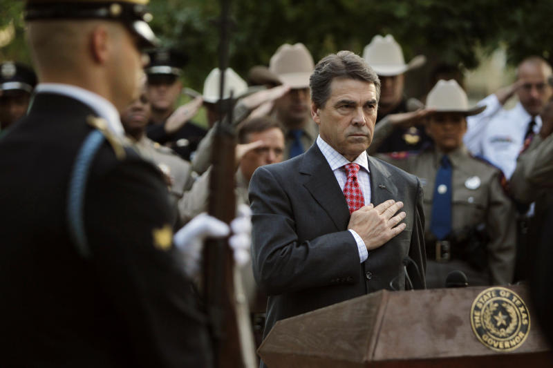 "Texas Governor Rick Perry and law enforcement personnel observe the playing of ""TAPS"" during a memorial service at the Texas State Cemetery Twin Towers Monument in Austin, TX, Sunday, Sep. 11, 2011.  America observed the 10th anniversary of the Sep. 11, 2001 terrorist attacks with remembrance services around the country.  (AP Photo/Erich Schlegel)"