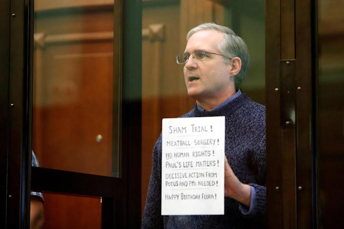 Image: Former U.S. Marine Paul Whelan, who was detained and accused of espionage, holds a sign as he stands inside a defendants' cage during his verdict hearing in Moscow, Russia (Maxim Shemetov / Reuters)