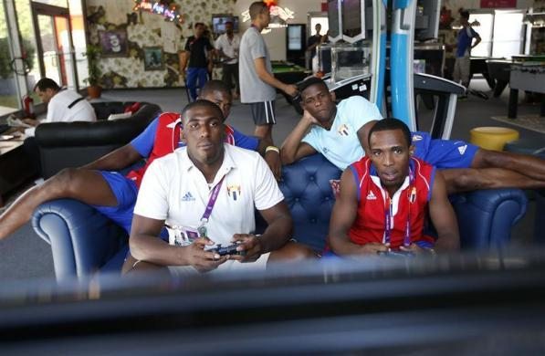Cuban wrestlers Yunior Estrada (L) and Hanser Meoque play a video game at the Athletes' Village at the Olympic Park in London, July 22, 2012. Opening ceremonies for the London 2012 Olympics will be held on Friday.