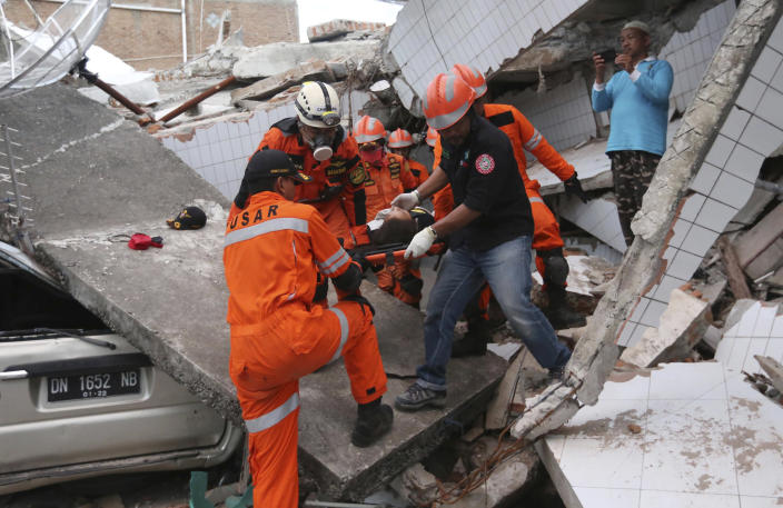 <p>Rescuers carry an earthquake survivor at restaurant building damaged following earthquakes and tsunami in Palu, Central Sulawesi, Indonesia, Sunday, Sept. 30, 2018. Rescuers were scrambling Sunday to try to find trapped victims in collapsed buildings where voices could be heard screaming for help after a massive earthquake in Indonesia spawned a deadly tsunami two days ago. (Photo: Tatan Syuflana/AP) </p>