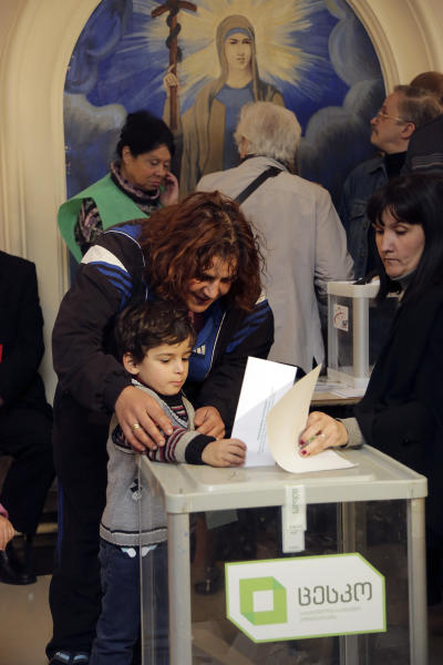Georgian woman and her son cast a ballot at a polling station in the presidential election in Tbilisi, Georgia, Sunday, Oct. 27, 2013. Georgians are voting Sunday for a president to succeed Mikhail Saakashvili, who during nearly a decade in power has turned this former Soviet republic into a fledgling democracy and a staunch U.S. ally. (AP Photo/Georgy Abdaladze)