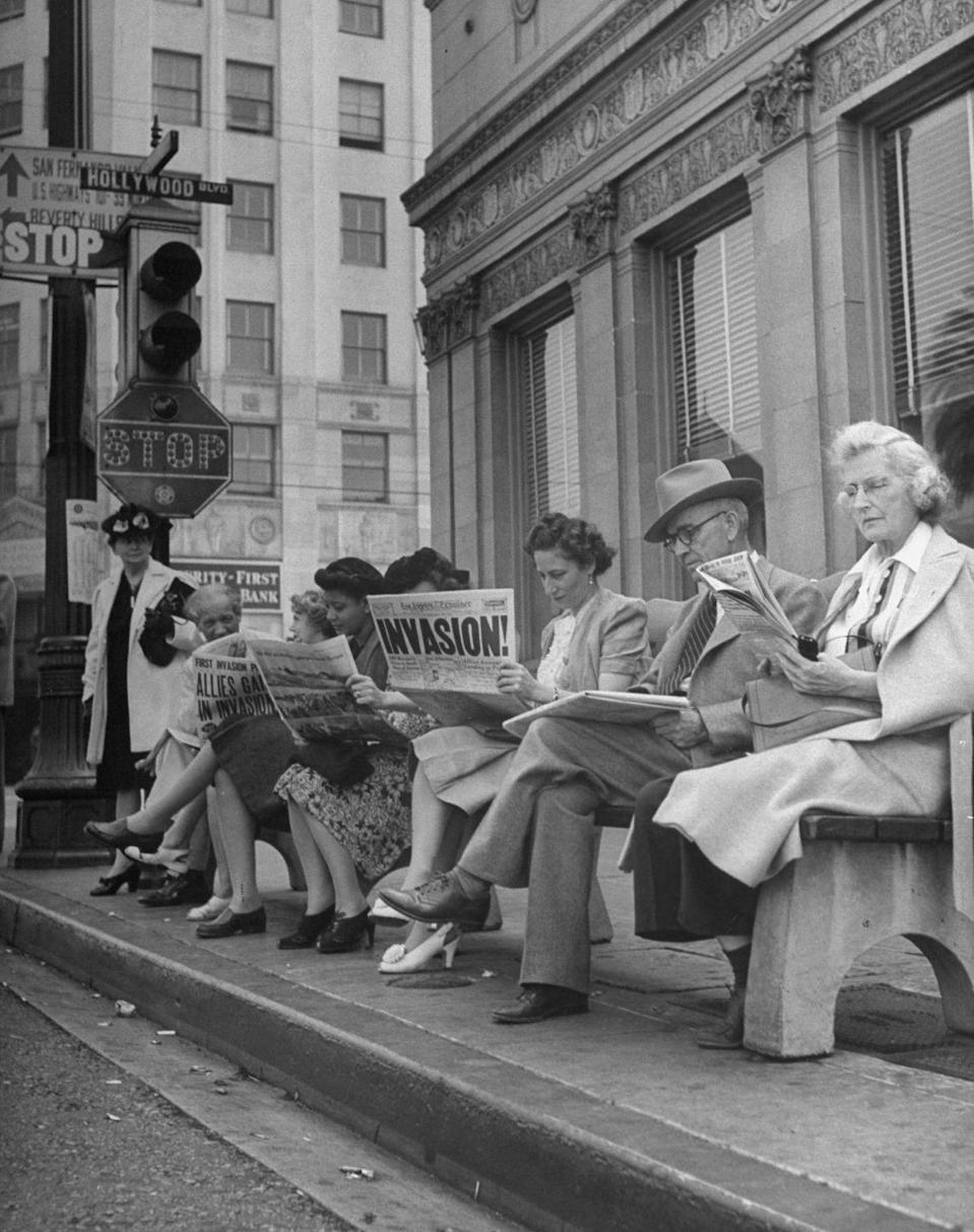 <p>A group of people waiting for the bus at the corner of Hollywood and Cahuenga Boulevards read about the D-Day invasion. <br></p>