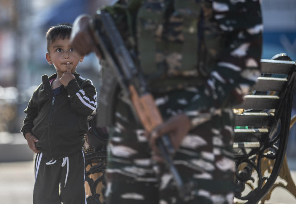 A Kashmiri child watches an Indian paramilitary soldier standing guard in Srinagar, Indian controlled Kashmir, Tuesday, Aug. 24, 2021. Indian government forces killed two senior rebel commanders and three other militants in two separate counterinsurgency operations in disputed Kashmir, police said Tuesday. (AP Photo/Mukhtar Khan)