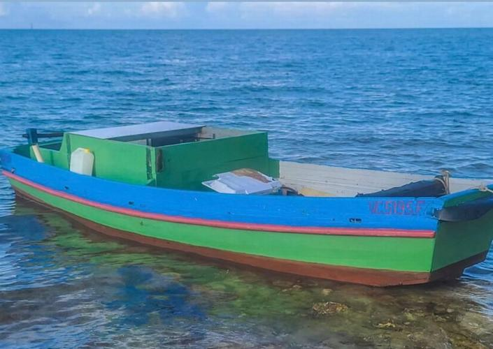 A wooden green boat floats in shallow water near Sombrero Beach in the Middle Florida Keys city of Marathon on Sunday, June 13, 2021. Four people from Cuba arrived in the Keys on the vessel earlier that day.