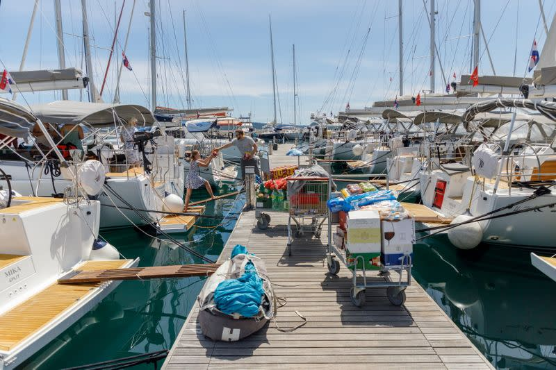 Tourists load supplies on a boat in the Kastel Gomilica marina