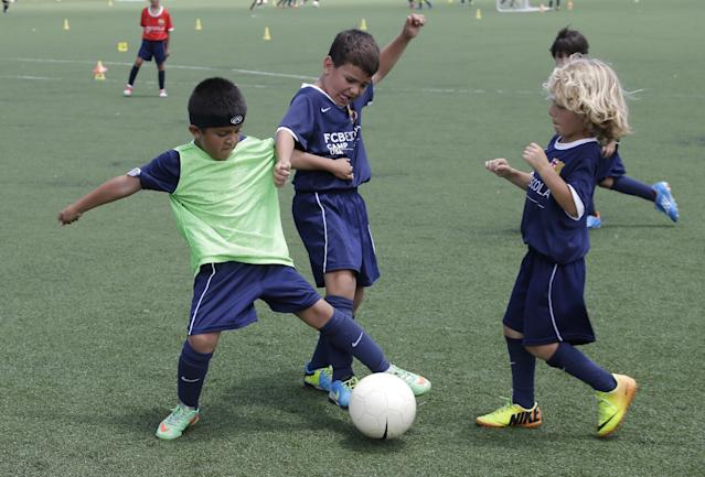In this Thursday, Aug. 1, 2014, photo, Toby Rafique, 6, left, of Dallas, fights for the ball during a soccer camp held by FC Barcelona in Miami. European clubs like Barcelona, Liverpool and Arsenal have long sent coaches to work at U.S. summer camps, but now some are opening year-round U.S. academies aimed at finding new talent but also to expand their fan bases. This is part of a number of initiatives of major teams to grow their brands in the U.S. (AP Photo/Lynne Sladky)