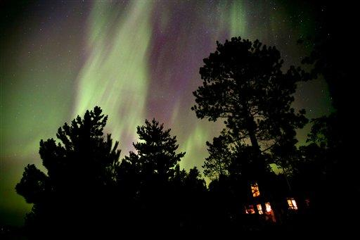 Northern Lights illuminate the sky over a cabin on Lake Elora in northern Minnesota early Sunday morning, July 15, 2012. (AP Photo/The Star Tribune, Brian Peterson)