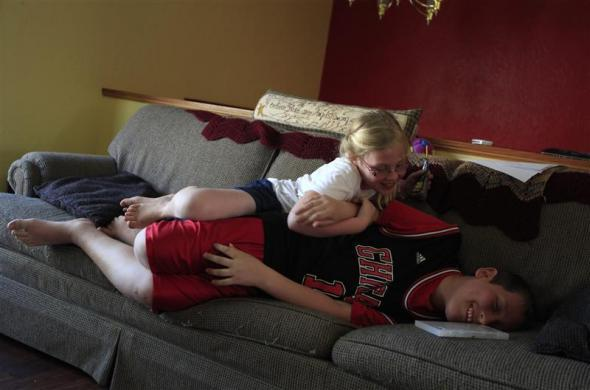 Parker Roos, who suffers from Fragile X, plays with his sister Allison on the couch at his home in Canton, Illinois, April 4, 2012.