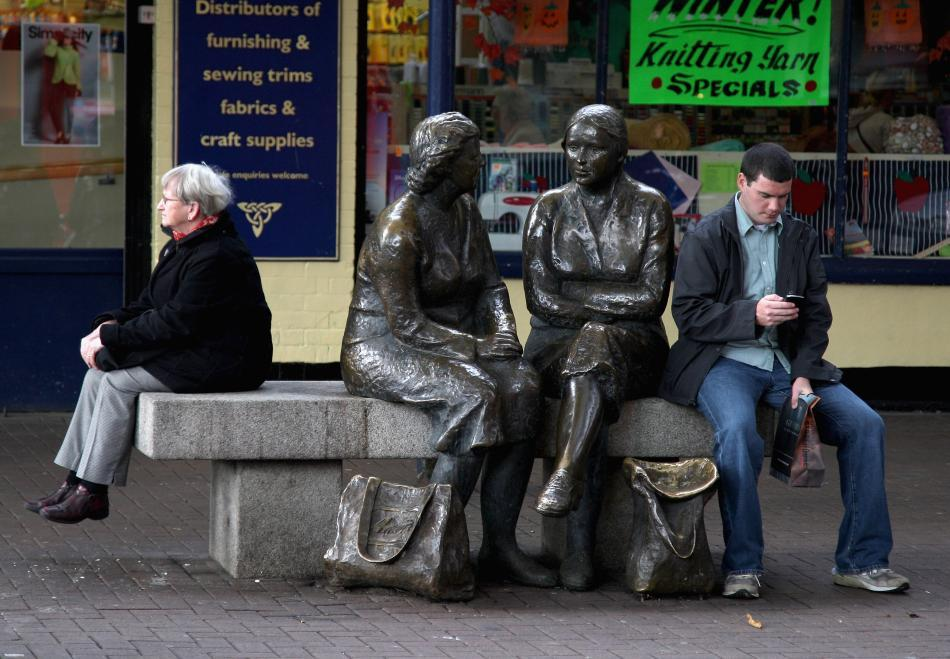 People take a break next to the sculpture on lower Liffey street known as the 'hags with the bags' in Dublin, Ireland.