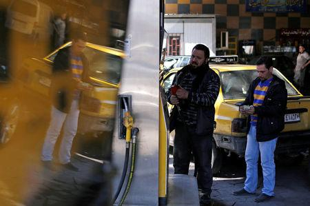 A man holds up a fuel pump nozzle at a petrol station in Damascus