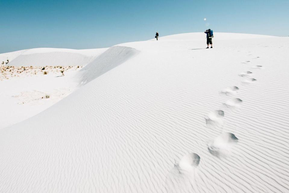 """<p>Cutting through New Mexico's Tularosa Basin, the dazzling dunes of <a href=""""https://www.nps.gov/whsa/index.htm"""" rel=""""nofollow noopener"""" target=""""_blank"""" data-ylk=""""slk:White Sands National Park"""" class=""""link rapid-noclick-resp"""">White Sands National Park</a> are composed of gypsum crystals. It's thought the sandy desert dates back to after the Ice Age when the climate began to warm causing the rain and snowmelt to dissolve the gypsum from the surrounding mountains and land in the basin. White Sands National Park was officially named a national park in 1933, bringing in nearly 600,000 visitors every year to hike the dunes and picnic in the sea of white sand. </p>"""